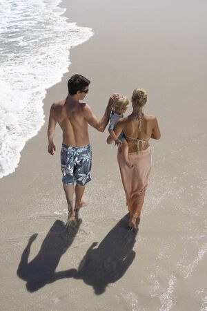 two generation family: Two generation family walking along beach, woman carrying daughter (2-4), rear view, elevated view