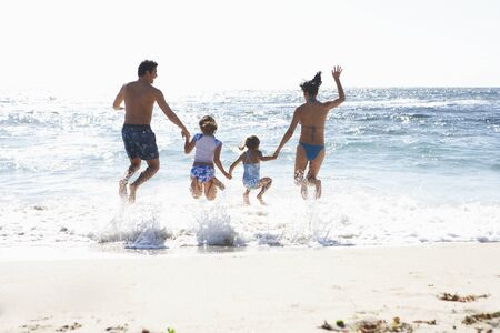 two generation family: Two generation family wearing swimwear, jumping above surf on sandy beach, side by side, holding hands, rear view, sunlight shimmering on sea