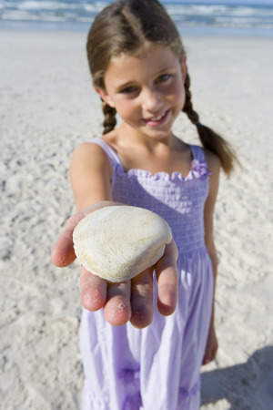 Girl (5-7) with shell on beach, smiling, portrait (differential focus) Stock Photo