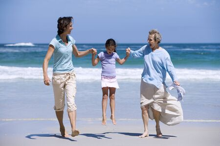 vacationing: Mother and grandmother swinging girl (7-9) on beach, smiling, front view