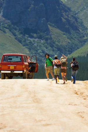 rucksacks: Four young adults, with rucksacks, running up to stationary on dirt track in mountain valley, rear view