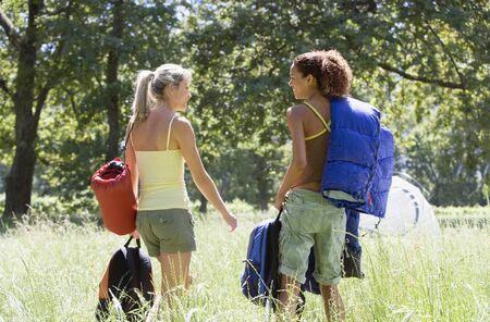 getting together: Two young women, with rucksacks and sleeping bags, departing on hiking trip in woodland clearing, rear view