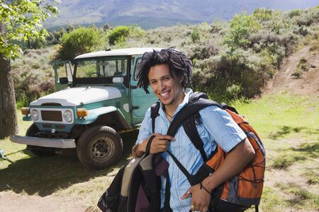 rucksacks: Young man unloading parked at start of camping holiday, carrying rucksacks, smiling, portrait