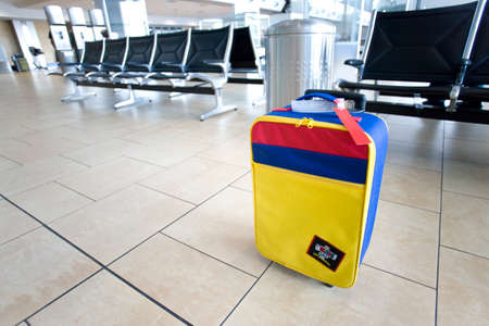 abandoning: Colourful, striped bag near empty seats in airport departure lounge