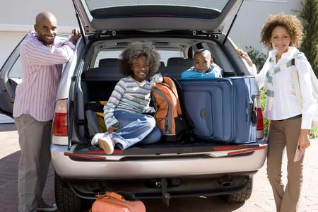 Mann und Frau, die von Sohn und Tochter (6-10) in der Rückseite des Autos mit Gepäck, Lächeln, Portrait