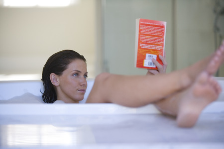 Young woman reading book in bubble bath
