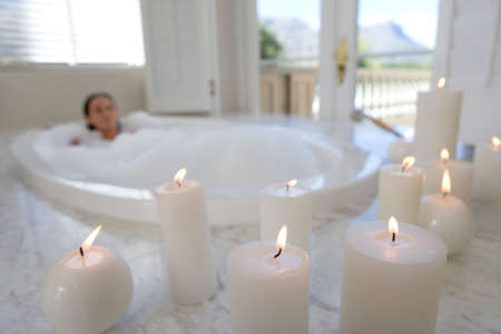woman in bath: Young woman in bubble bath, illuminated candles in foreground LANG_EVOIMAGES