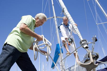 uomini maturi: Due uomini maturi che si preparano a salpare su yacht, un uomo svincolo cima di ormeggio, sorridente, basso