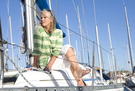legs crossed at knee: Mature woman, in green striped jumper, sitting on deck of yacht moored at harbour jetty, legs crossed at knee, looking away, thinking
