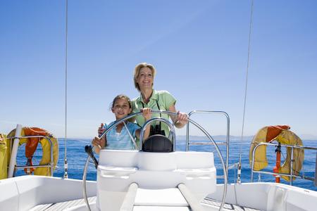 timon barco: Madre e hija (8-10) de pie en el tim�n del barco de vela en el mar, de direcci�n, sonriendo, vista frontal, retrato LANG_EVOIMAGES