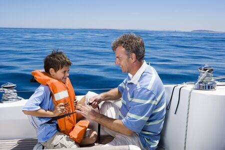 boat deck: Father and son (8-10) sitting on deck of sailing boat out at sea, boy wearing orange life jacket, man tying strap, smiling, side view