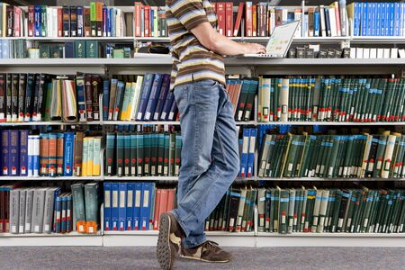 only one teenage boy: Young man studying in library, side view (low section) LANG_EVOIMAGES