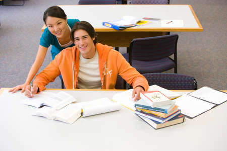 elevated view: Young woman standing behind young man studying in library, smiling, portrait, elevated view LANG_EVOIMAGES