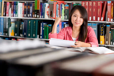 one teenage girl only: Woman studying in library, smiling, portrait