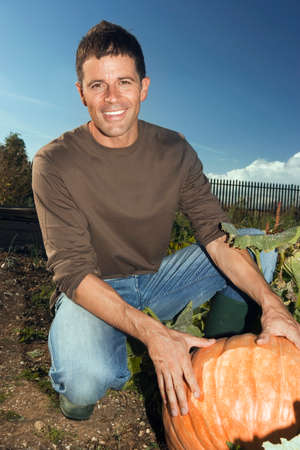 large pumpkin: Man kneeling beside large pumpkin in vegetable garden, smiling, portrait