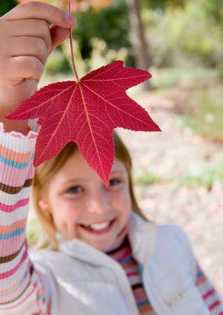 holding aloft: Girl (7-9) holding aloft red maple leaf in park in autumn, smiling, close-up, portrait