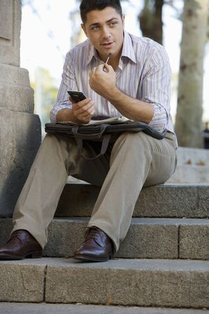 one mid adult man only: Businessman sitting on steps, holding personal electronic organiser, briefcase in lap, outdoors LANG_EVOIMAGES