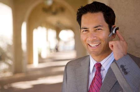 earpiece: Businessman standing in building arcade, using hands-free mobile phone earpiece, smiling, portrait