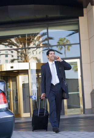 telephoning: Businessman leaving hotel with luggage in tow, using mobile phone, smiling