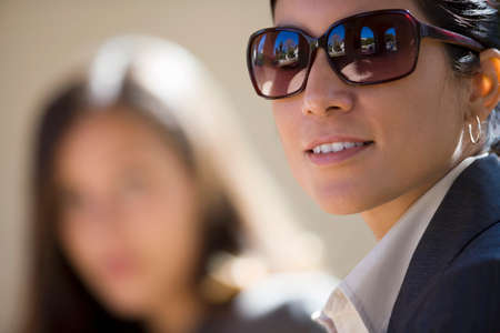 only mid adult women: Two businesswomen outdoors, focus on woman wearing sunglasses in foreground, smiling, side view, portrait