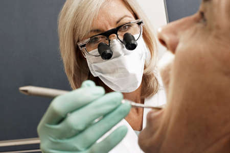 surgical tool: Female dentist wearing surgical loupes and mask, examining patient, using dental tool, close-up LANG_EVOIMAGES