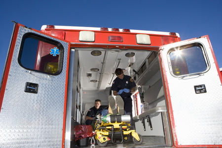 Paramedics with man on stretcher in ambulance, low angle view Stock Photo