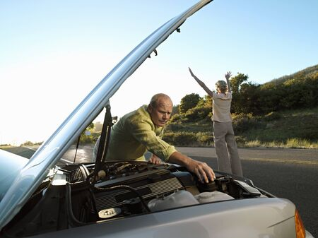 hailing: Senior man checking car engine at roadside, woman hailing oncoming traffic on country road