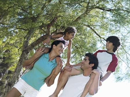 two generation family: Two generation family walking in park, children (6-11) on parents shoulders, smiling (tilt)