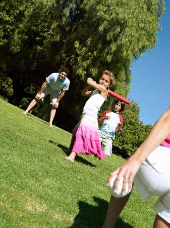 two generation family: Two generation family playing softball in park, girl (6-8) batting, smiling (tilt)