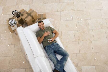 cardboard only: Man moving house, lying on white sofa, taking tea break, smiling, portrait, overhead view LANG_EVOIMAGES