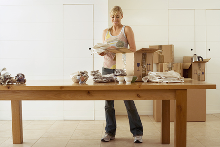 cardboard only: Woman moving house, packing crockery in cardboard boxes on dining room table, smiling, front view LANG_EVOIMAGES