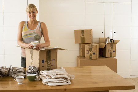 cardboard only: Woman moving house, packing crockery wrapped in paper in box on dining room table, smiling, portrait