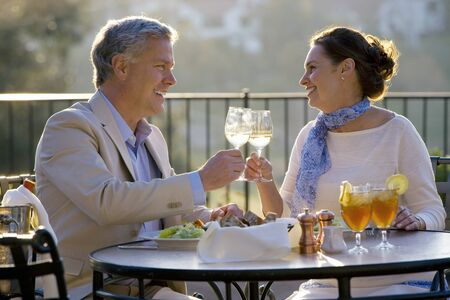 couple dining: Mature couple dining at outdoor restaurant table, making celebratory toast with wine glasses, smiling, side view