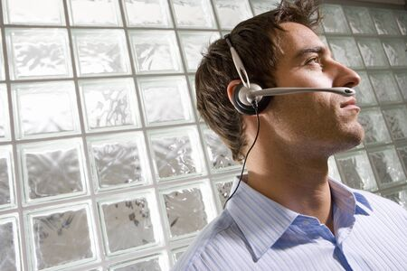 glass block: Young businessman wearing headset by glass block wall, low angle view (tilt)