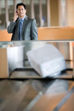 differential focus: Businessman using mobile phone, smiling, portrait (differential focus)