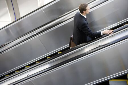 elevated view: Businessman ascending escalator, side view, elevated view LANG_EVOIMAGES
