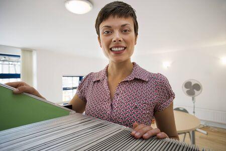 office cabinet: Female office worker standing beside filing cabinet, smiling, portrait