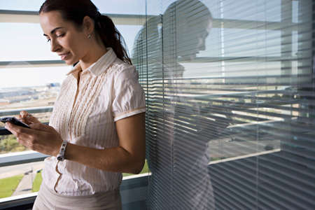 electronic organiser: Businesswoman leaning against office window, using personal electronic organiser, side view