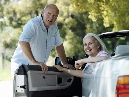 transportation: Senior couple posing beside convertible car, woman sitting in drivers seat, smiling, portrait