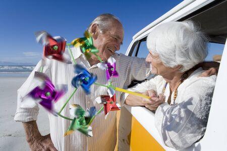 beach window: Senior man embracing woman with pinwheel through window of camper van on beach, smiling LANG_EVOIMAGES