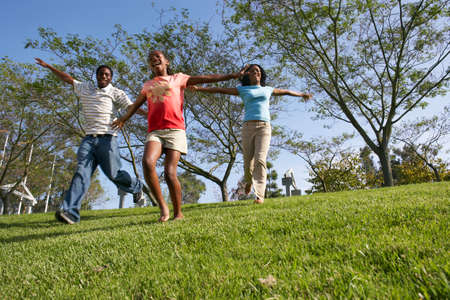two generation family: Two generation family running down hill in park, arms outstretched, smiling, surface level LANG_EVOIMAGES