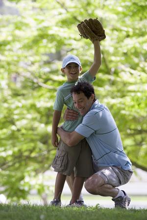 guante de beisbol: Padre jugando con hijo (10-12) en el parque, ni�o con guante de b�isbol, mano en alto, sonriente, retrato