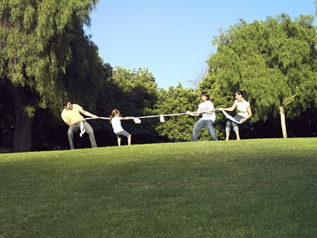 two generation family: Two generation family playing tug-of-war on grass in park, side view