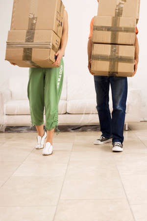 low section view: Couple moving house, carrying stack of cardboard boxes, side by side, low section, front view LANG_EVOIMAGES
