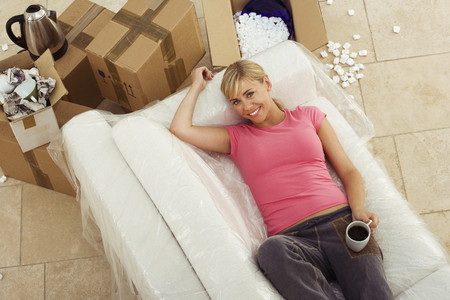 cardboard only: Woman moving house, lying on white sofa, taking tea break, smiling, portrait, overhead view LANG_EVOIMAGES
