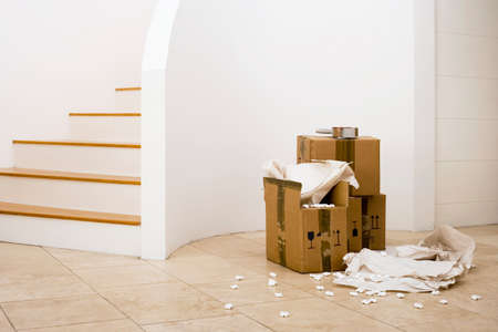 abandoning: Small stack of boxes, paper and packing foam beside staircase in sparse room