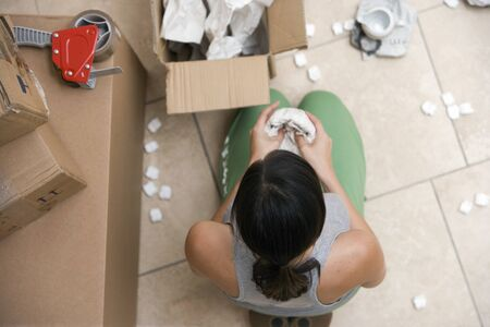 cardboard only: Woman sitting on floor, packing box, wrapping bowl in paper, overhead view