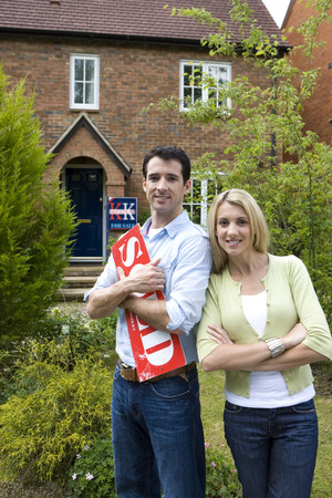 Young couple outside house, man with sold sign, smiling, portrait LANG_EVOIMAGES