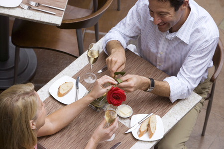 couple dining: Couple dining in restaurant, man giving woman red rose, elevated view LANG_EVOIMAGES