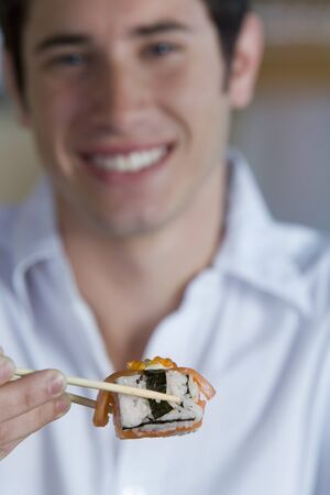 differential focus: Young man eating sushi with chopsticks, smiling, portrait (differential focus)